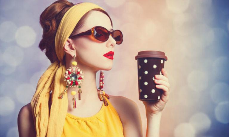 Frau im 70er Jahre Look mit gelbem Haarband und bunten Ohrringen