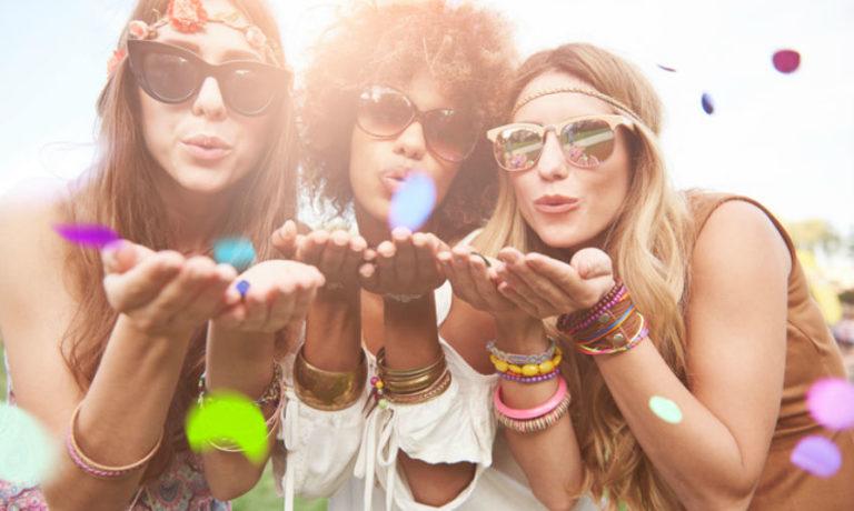 Drei Frauen auf einem Festival mit bunten Accessoires