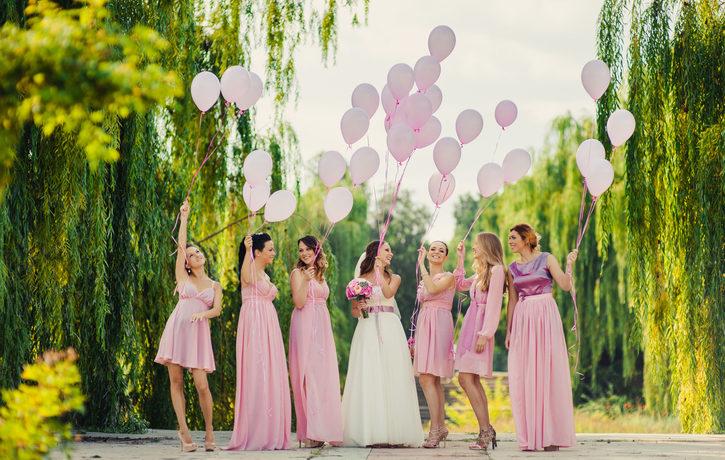 Eine Braut lässt mit ihren 6 Trauzeuginnen in rosa Kleidern Luftballons steigen