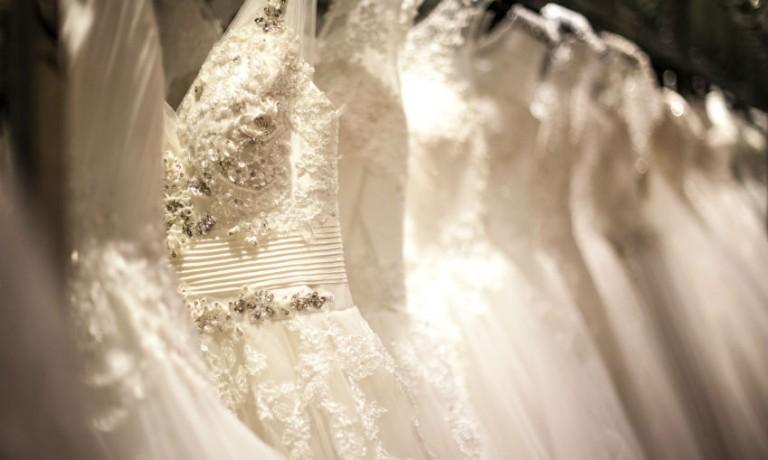 mehrere aufgehängte Brautkleider hintereinander