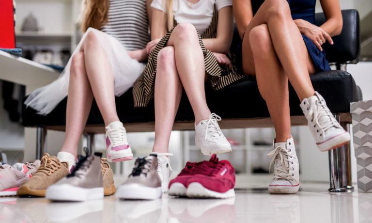 Drei Frauen sitzen auf einer bank und präsentieren ihre Schuhe