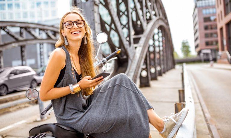 Frau im Every-Day Look posiert für Foto auf Brücke