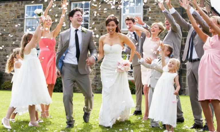 Was trägt man zur Hochzeit als Gast? Gäste werfen Konfetti auf Braut und Bräutigam