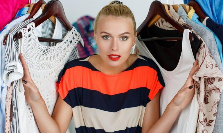Junge blonde Frau steht zwischen ihren Klamotten