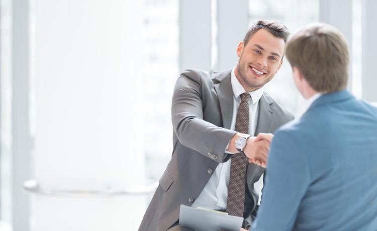 Mann mit einem Anzug und einer Krawatte schüttelt einem anderen Mann in einem hellen Raum lächelnd die Hand