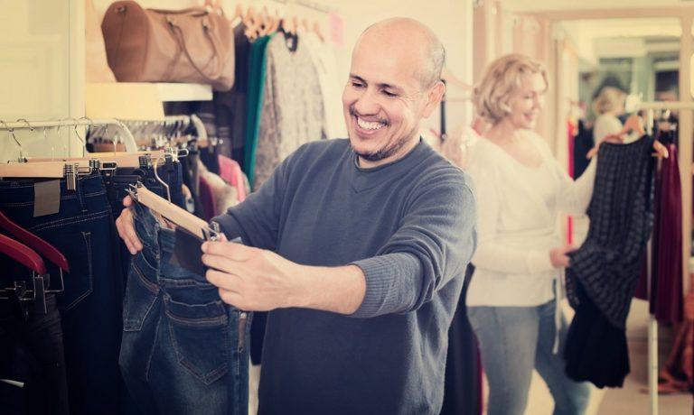 Mann hält im Laden einen Jeanshose in der Hand