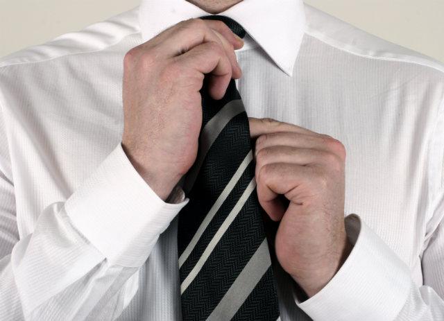 Mann rückt seine Krawatte zurecht
