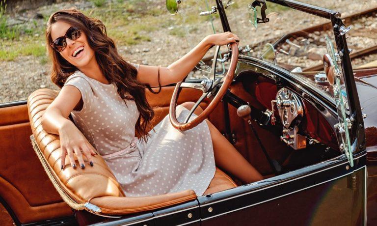 Junge Frau im gepnkteten Sommerkleid in Oldtimer