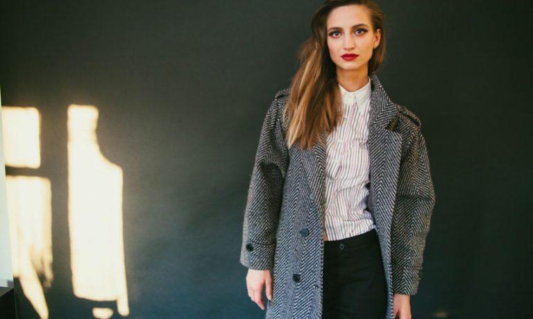 Frau in Mantel und Bluse mit Muster