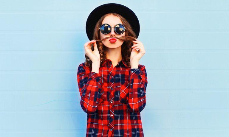 Junge Frau in rot-blauer Karobluse mit Sonnenbrille und Hut