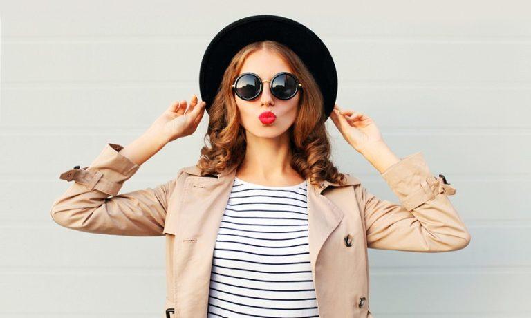 Junge Frau mit Hut, Sonnenbrille und Trenchcoat macht Kussmund in die Kamera