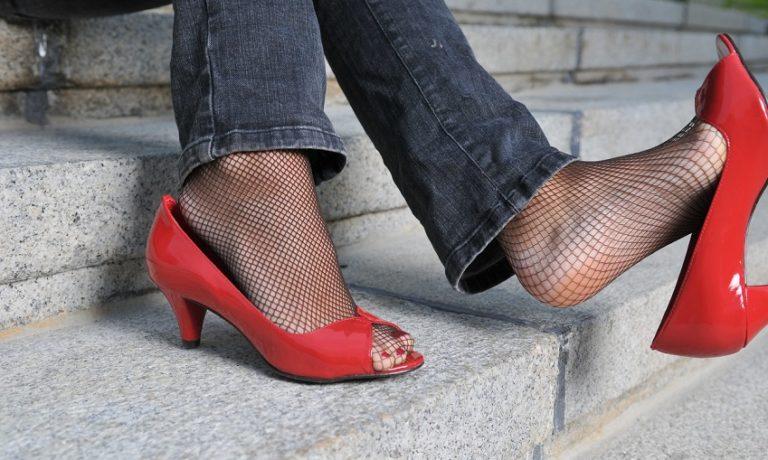 Füße einer Frau mit Netzstrümpfen und roten High Heels