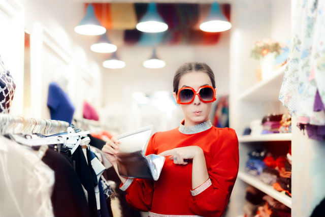 Outlet sparen - Frau mit großer Sonnenbrille und Designer-Clutch in der Hand zieht lustige Grimasse