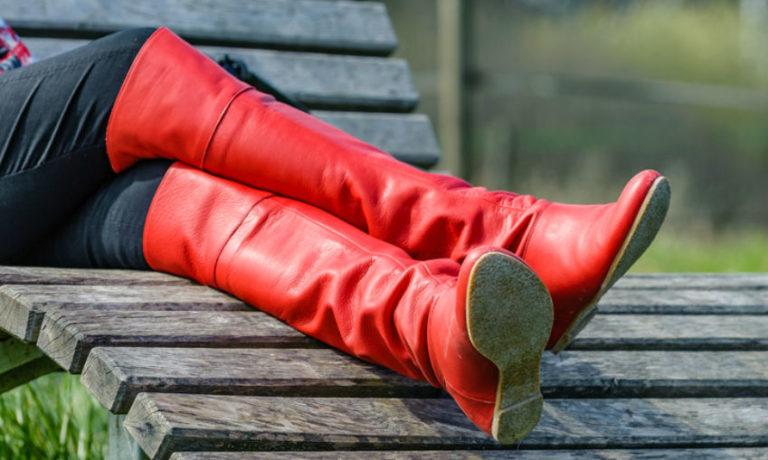Frau mit roten Overknee Stiefel, die mit einer dunklen Jeans kombiniert sind