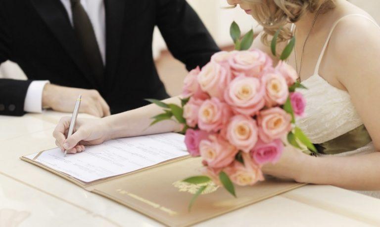 Brautpaar beim Unterscheiben des Ehevertrages