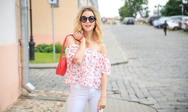 Junge Frau posiert in schulterfreier Bluse und mit Sonnenbrille