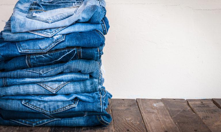 Ein Stapel aus Jeans-Hosen auf einem Holzgrund
