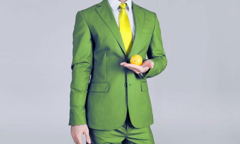Mann im grünen Anzug mit gelber Krawatte und Zitrone in der Hand