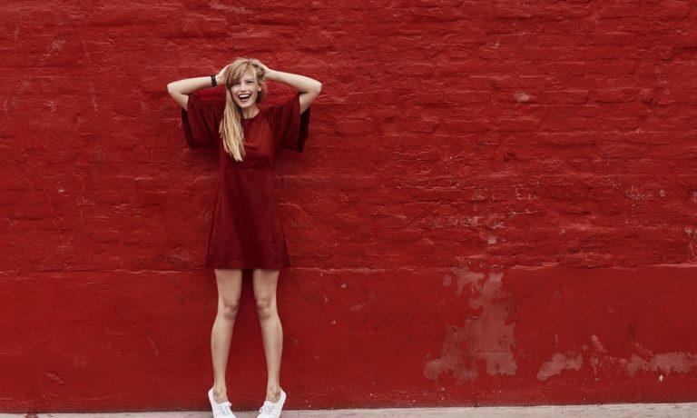 Junge Frau in rotem Kleid vor roter Wand