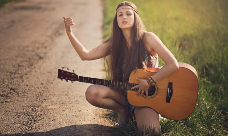 Hippie Hipster Mädchen wartet als Anhalterin mit einer Gitarre an einer Straße