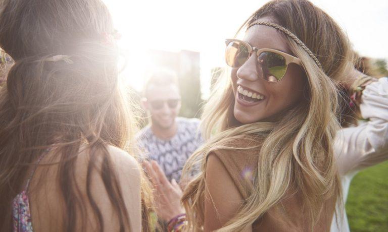 Blondes Mädchen mit Sonnenbrille tanzt mit ihren Freunden auf einem Musik-Festival