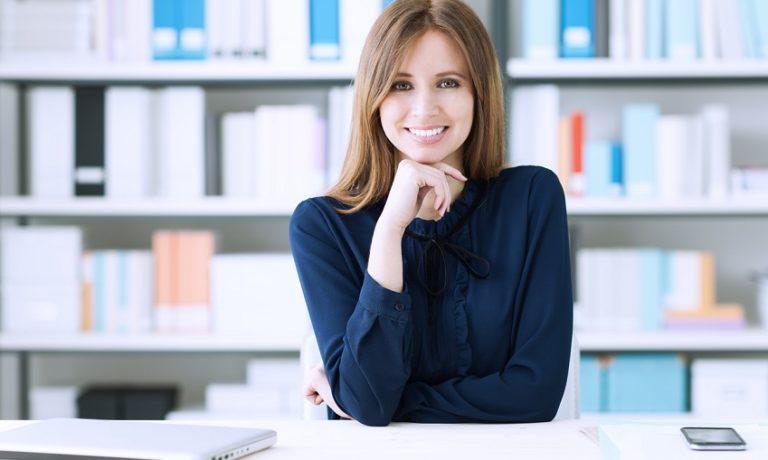 Frau am Schreibtisch mit dunkelblauer Bluse