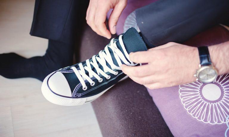Mann im Anzug bindet sich im Sitzen die Schnürsenkel seines linken Sneakers zu