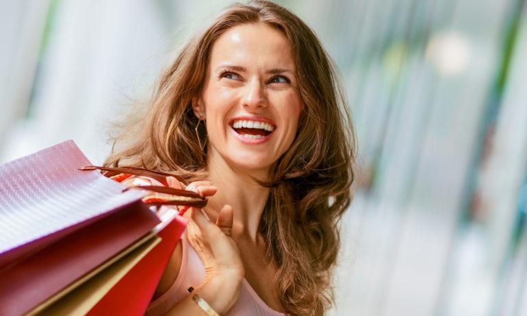 Lachende Frau mit Einkaufstaschen in der Hand
