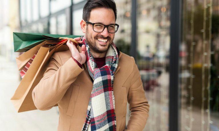 Mann mit Einkaufstaschen über seiner Schulter
