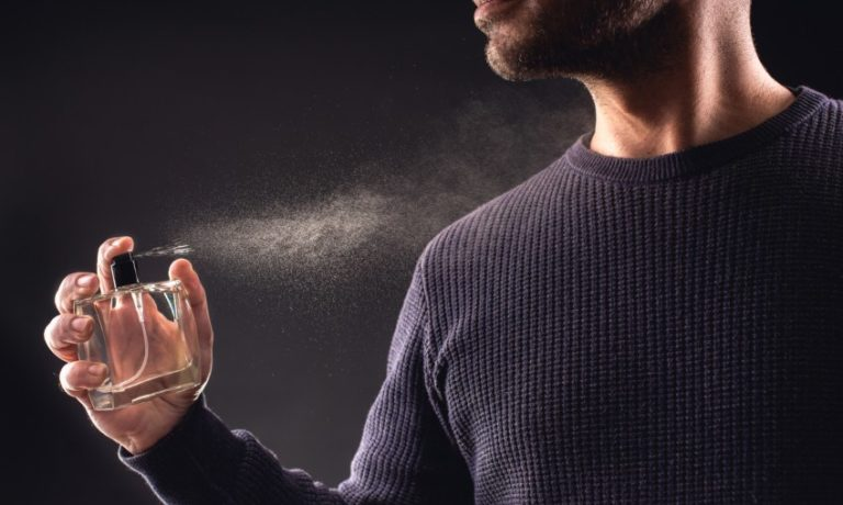 Mann trägt Parfum auf