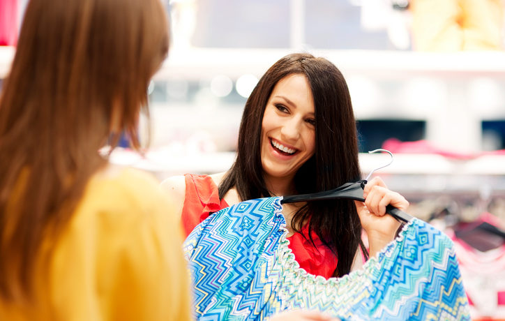 Frau zeigt Freundin Klamotten im Geschäft