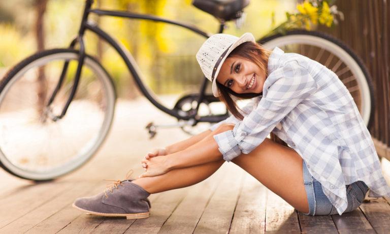 Junge Frau in Shorts sitzt vor einem Fahrrad
