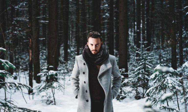 Mann, der im verschneiten Wald steht