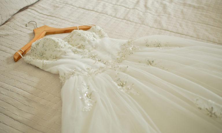 Weißes Hochzeitskleid auf weißem Bettlacken