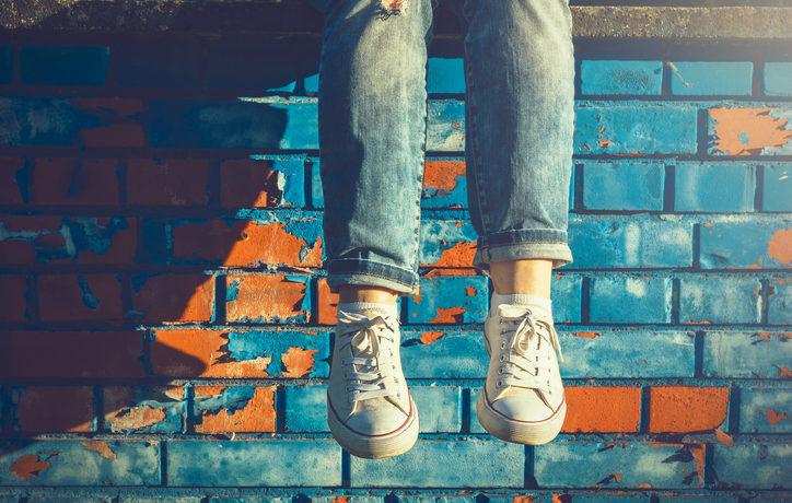 Beine einer Frau mit hochgekrempelter Jeans bis zum Knöchel vor einer Mauer