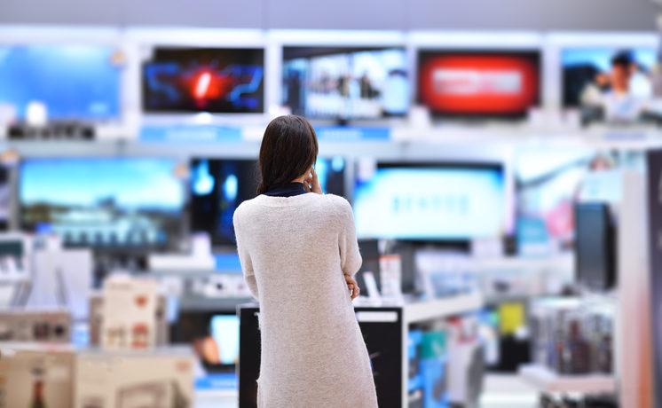 Frau steht vor einer großen Auswahl Fernseher