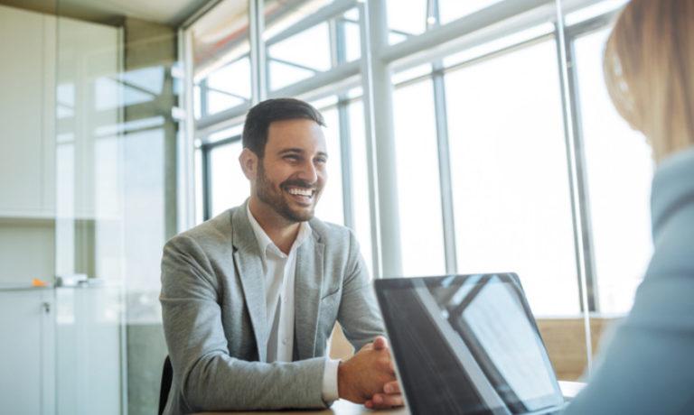Junger Mann im Bewerbungsgespräch ohne Krawatte mit Anzug