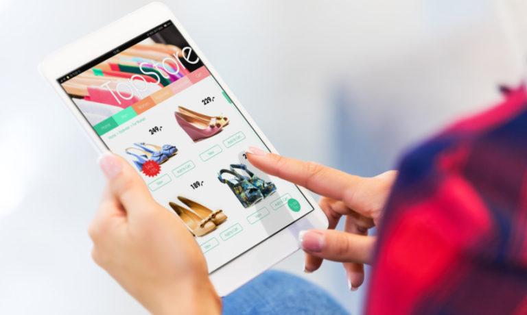 Eine Frau shoppt am Tablet Kleidung