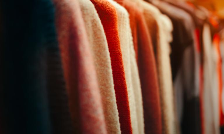 Mehrere Oberteile in herbstlichen Farben aufgehängt auf einem Kleiderständer