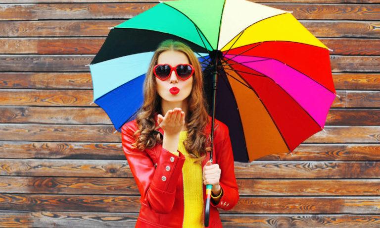 Junge Frau in roter Lederjacke hält einen bunten Regenschirm